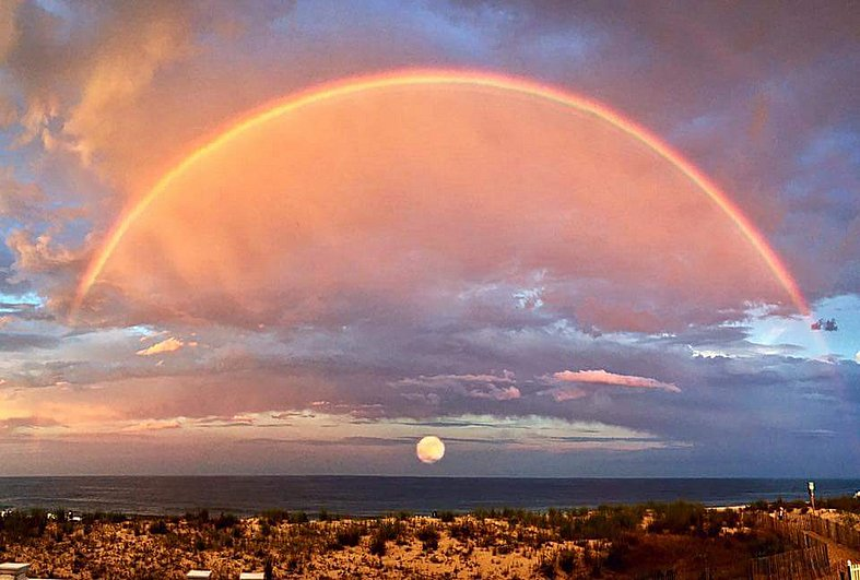 A perfect rainbow, the moon and sea all in one picture
